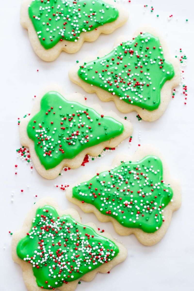 Cookies cut out in the shape of Christmas trees are decorated with green frosting and sprinkles.