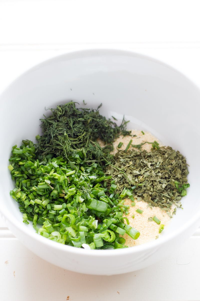 Spices and herbs for homemade ranch dressing in a white bowl