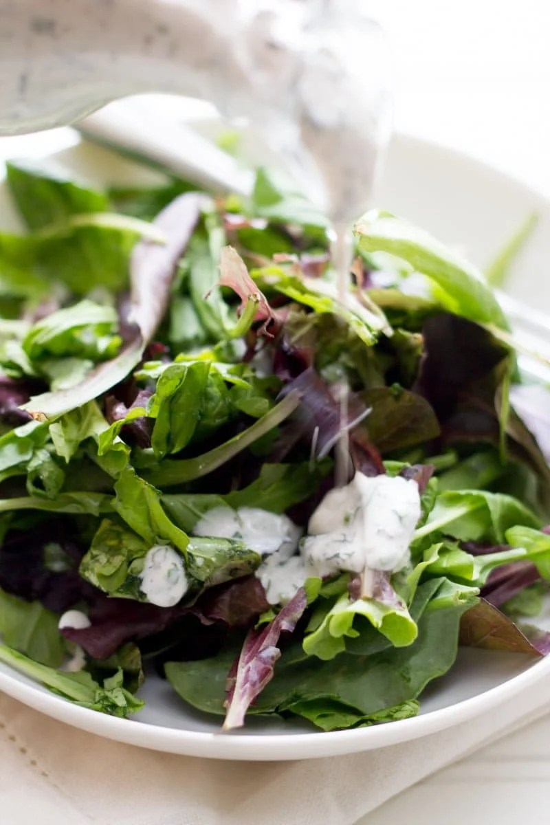 Close up of a bowl of salad with ranch dressing in a white bowl.