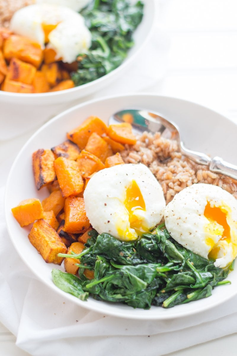 A white bowl filled with farro, roasted sweet potatoes, sauteed greens, and poached eggs