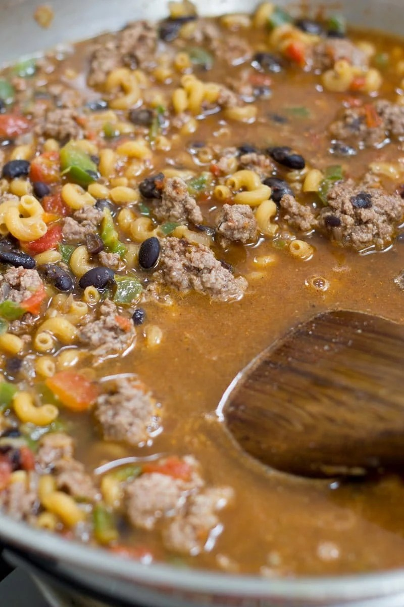 Pasta, black beans, beef and other ingredients cook together in a silver pan. A wooden spoon stirs the mixture.