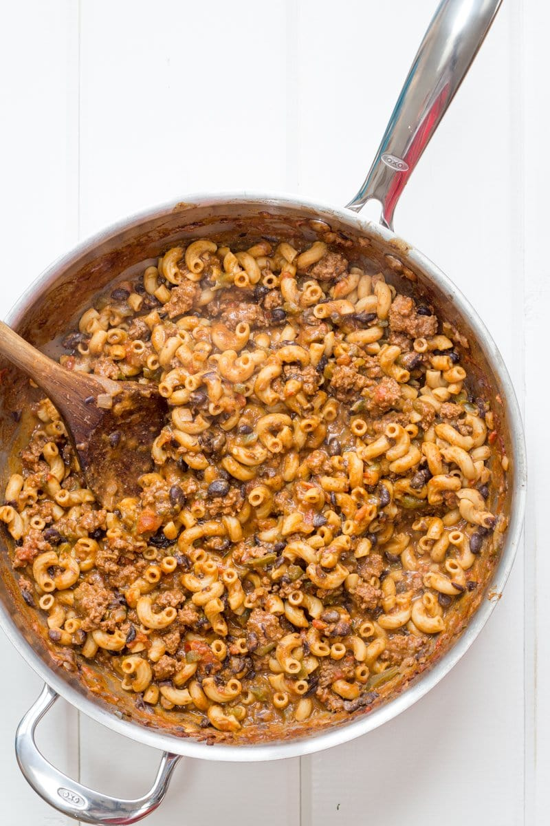 A pot of taco pasta skillet with a wooden spoon stirring it.