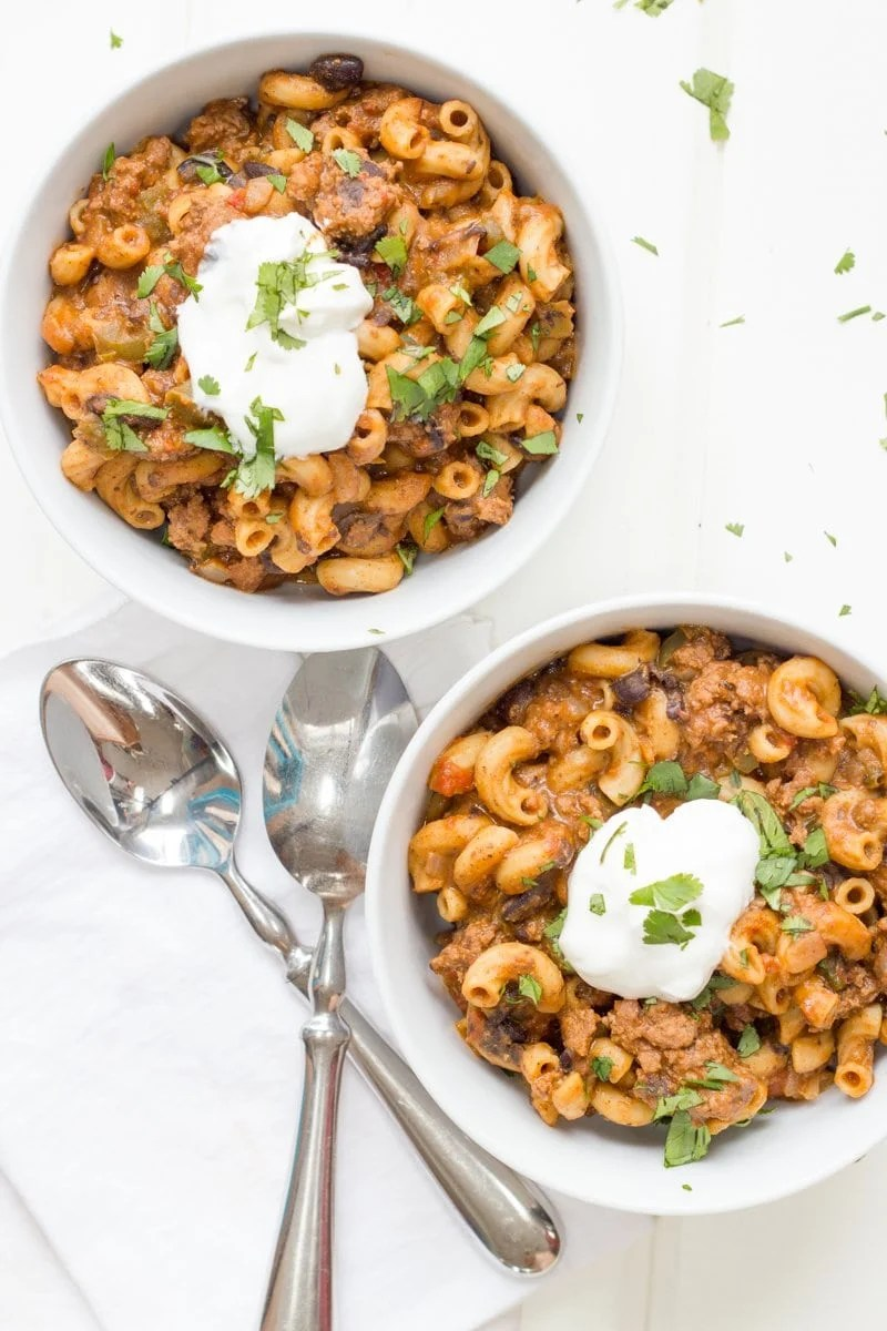Two bowls of the taco macaroni skillet sit on a white background. Two spoon sit nearby on a white napkin.