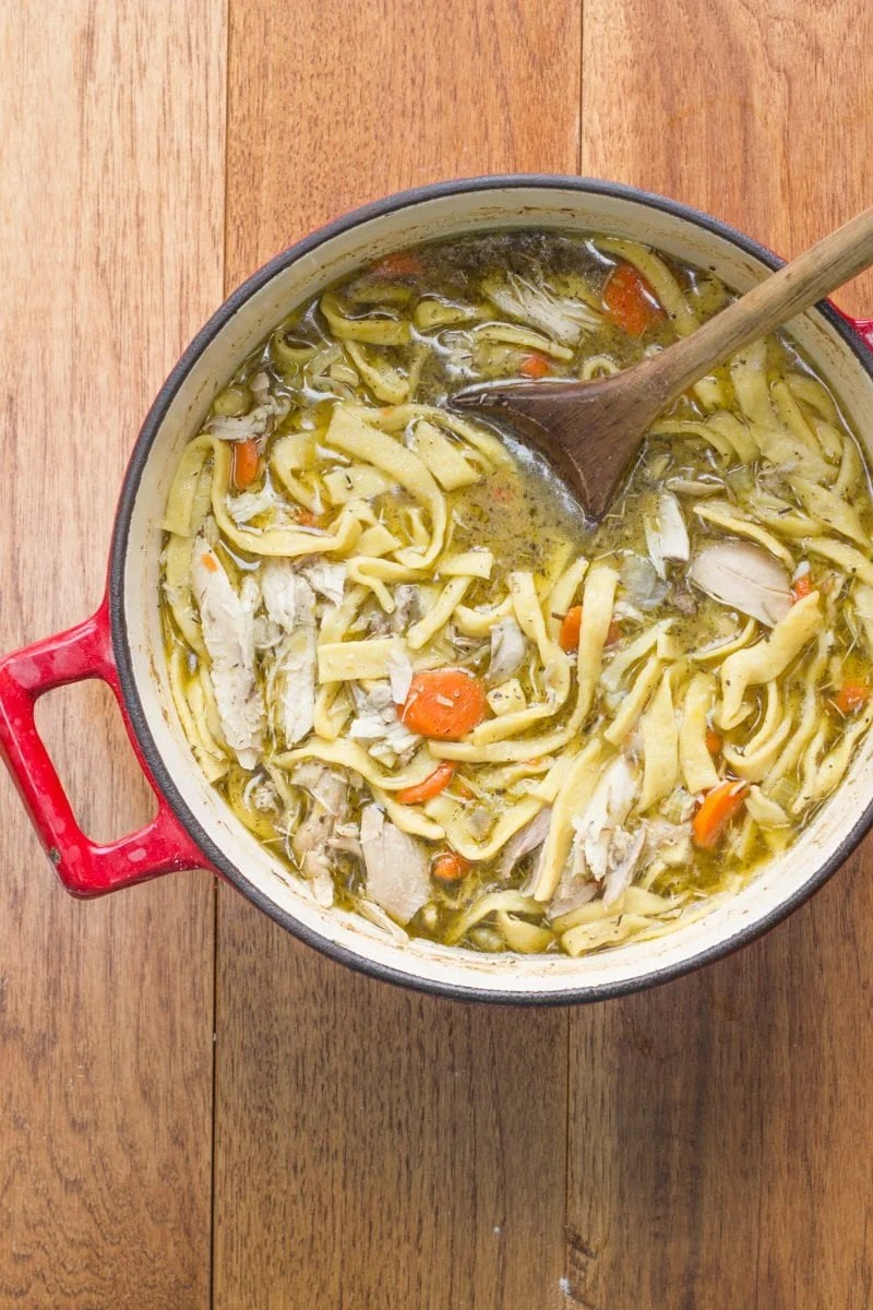 Chicken Noodle Soup From Scratch in a red Dutch oven, with a wooden spoon set in the soup.