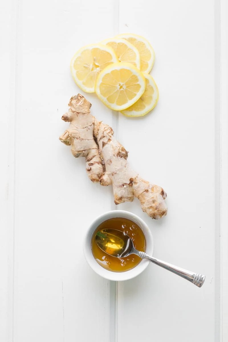 Ingredients for lemonade sit together - ginger, honey and lemons.