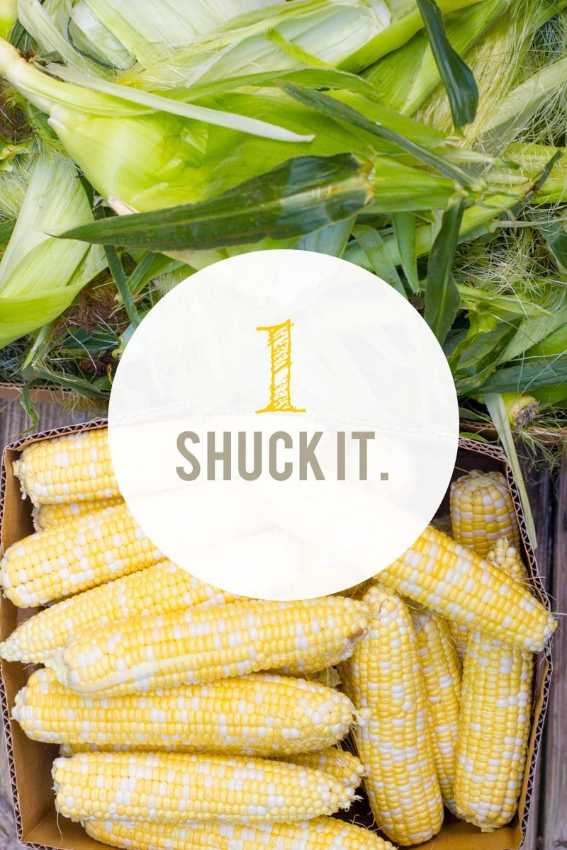 "Box full of corn, with the silks nearby. A text overlay reads ""1. Shuck It."""