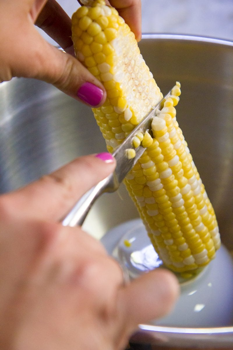 Hands using a knife to cut corn off a cob over a metal bowl.