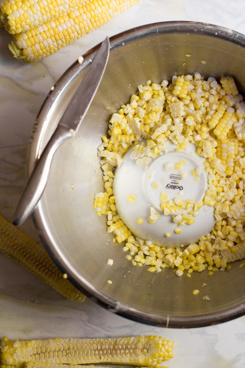 Knife resting on the edge of a metal bowl filled with corn kernels.