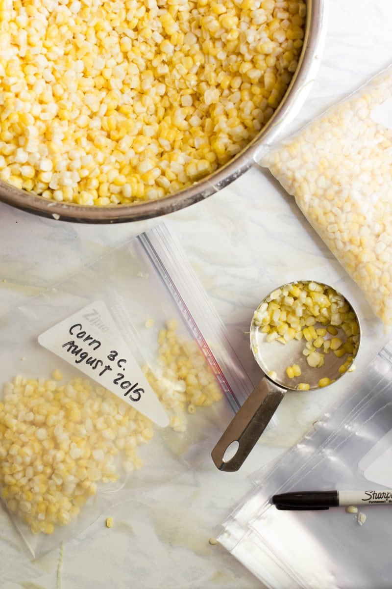 Metal bowl filled with corn kernels. A metal measuring cup is being used to move corn to zip-top bags.