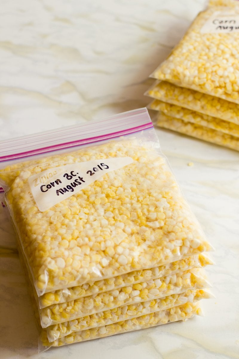 Five zip-top bags filled with 3 cups of fresh corn kernels labeled and stacked on a countertop.