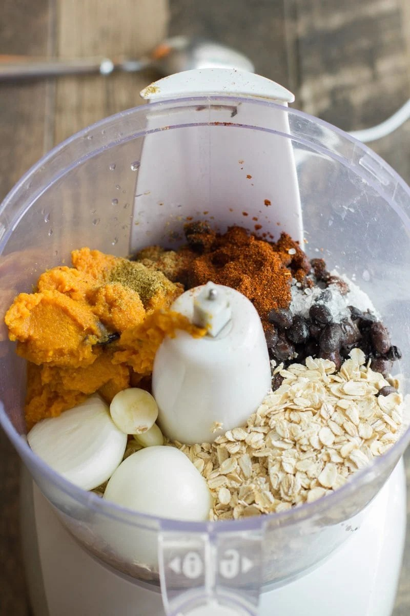Ingredients to make burgers sits in a food processor - oatmeal, sweet potato, onion, seasonings and sweet potatoes.