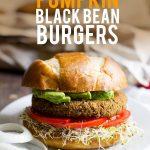 "A Pumpkin Black Bean Burger sits on a white plate. A text overlay reads ""vegan pumpkin black bean burgers"""