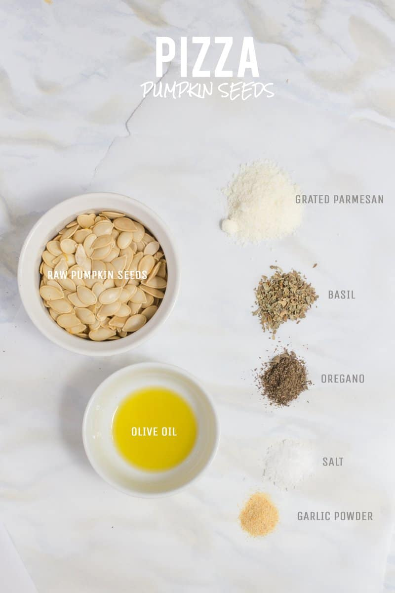 All ingredients for Pizza flavored roasted pumpkin seeds are laid out on a white marble countertop.