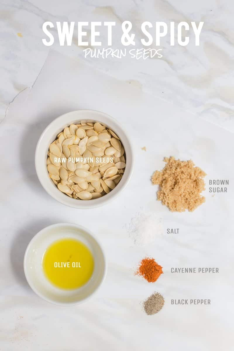 All ingredients for Sweet and Spicy flavored roasted pumpkin seeds are laid out on a white marble countertop.
