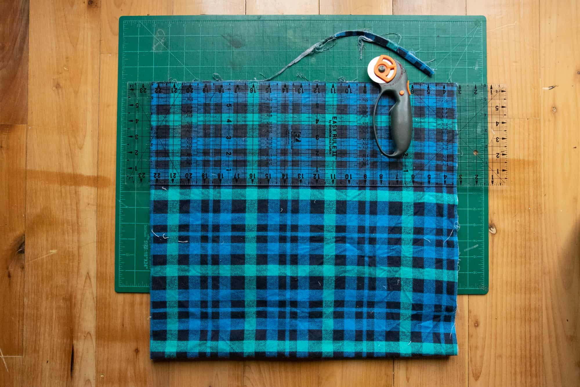 A piece of blue, black, and teal plaid flannel fabric is folded into quarters and placed on a cutting. A rotary cutter and ruler are used to cut straight lines for a DIY blanket scarf.