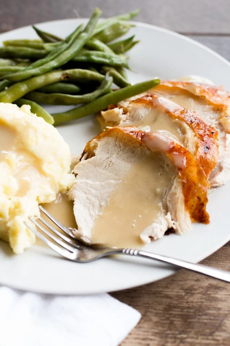Slices of roasted turkey covered with gravy, on a plate with mashed potatoes and green beans