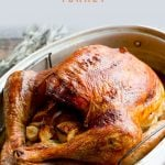 "Whole Roasted Turkey in a metal roasting pan. A text overlay reads ""How to Dry Brine a Thanksgiving Turkey."""