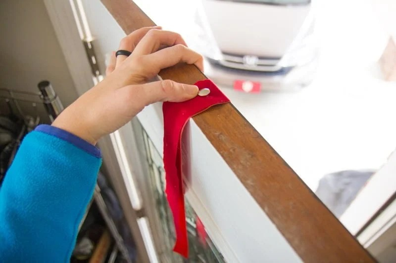 Hand pushing a thumbtack into a ribbon on top of a wooden door