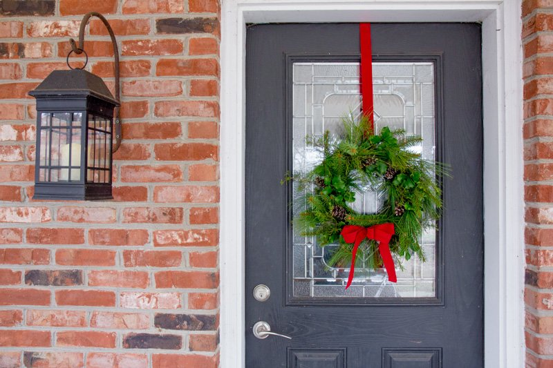 Evergreen wreath hanging from a red ribbon on a front door of a brick house.