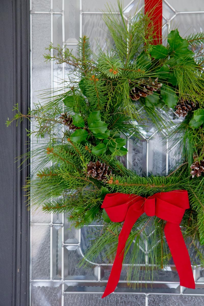 Close Up of an evergreen wreath hanging from a red ribbon on a front door.
