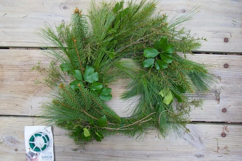 Wreath form almost completely covered in evergreens