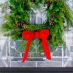 "Evergreen wreath hanging from a red ribbon on a front door. Text overlay reads ""How to Make a Fresh Greenery Wreath in Less Than 30 Minutes."""