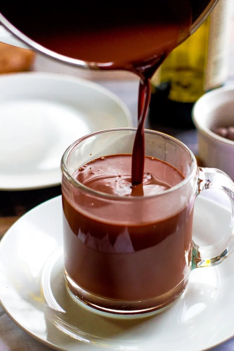 Red Wine Hot Chocolate being poured from a pot into a clear glass mug