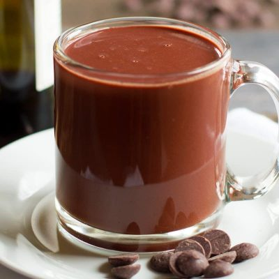 Clear glass mug of Red Wine Hot Chocolate on a white saucer with chocolate chips
