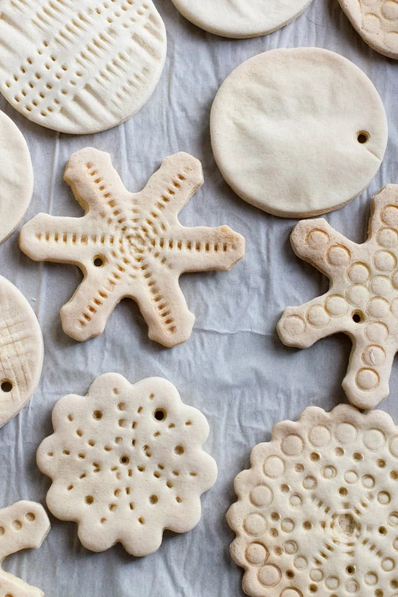 Tight view of various shapes of baked, undecorated salt dough ornaments.