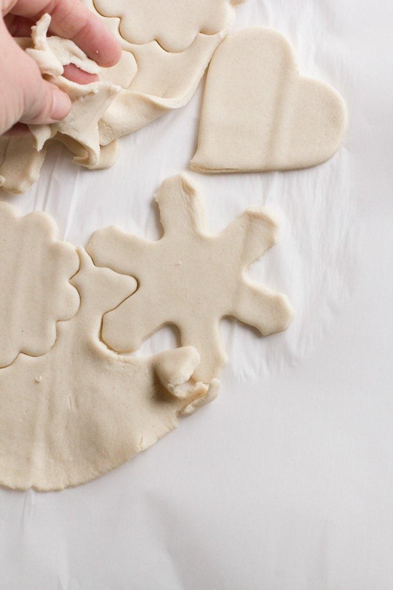 A hand peels away excess salt dough scraps from around cut out salt dough ornament shapes.