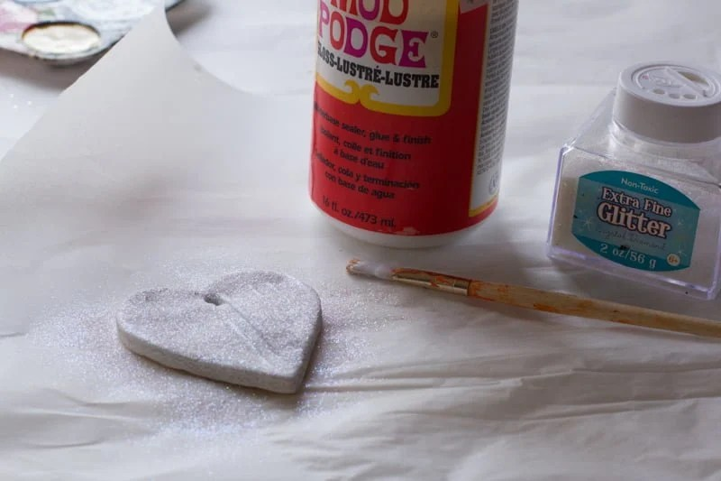 A salt dough ornament covered in white glitter sits on a white background with a bottle of Mod Podge and glitter in the background.