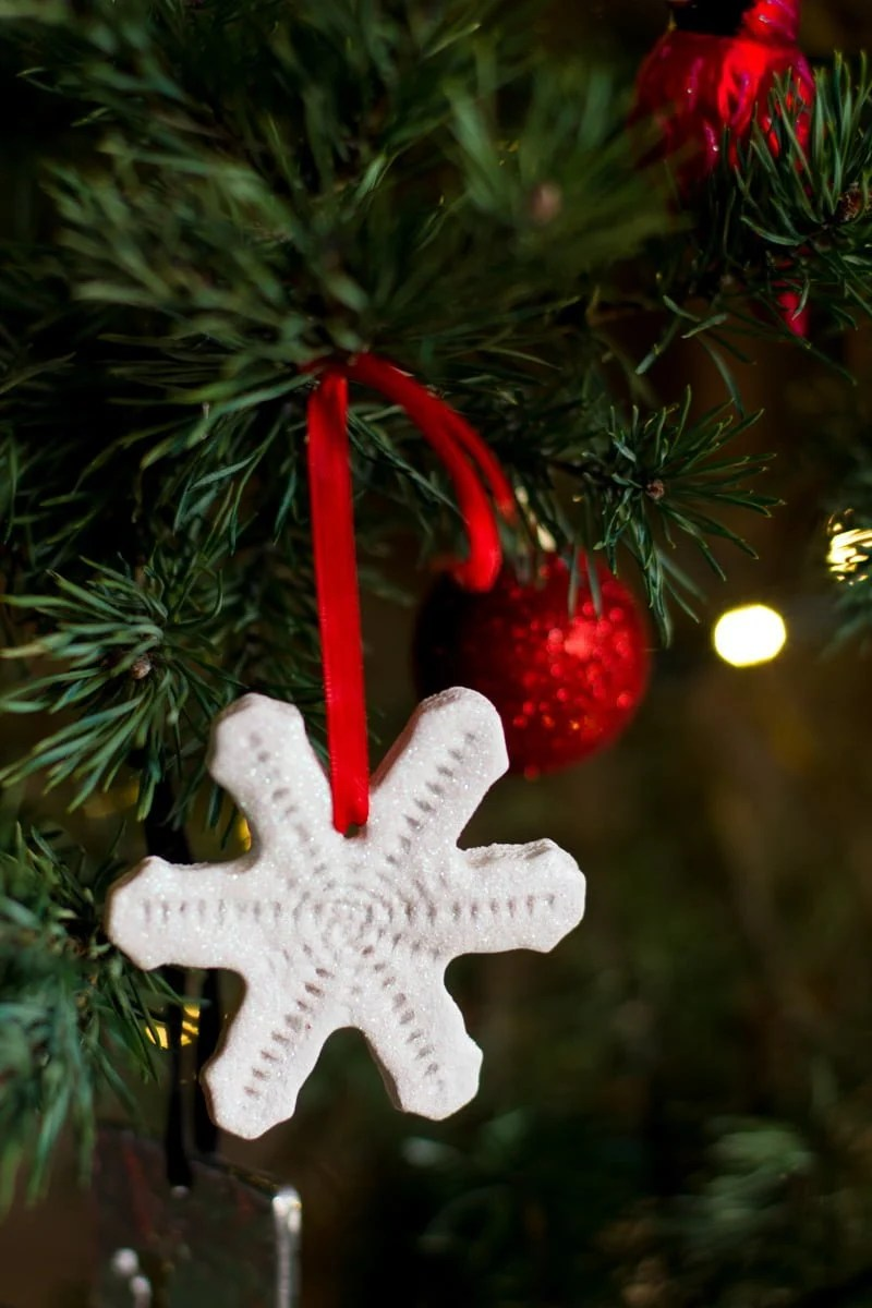 A sparkly snowflake shaped salt dough ornament hangs from a Christmas tree with a red ribbon. Christmas lights and red sparkly ornaments are blurry in the background.