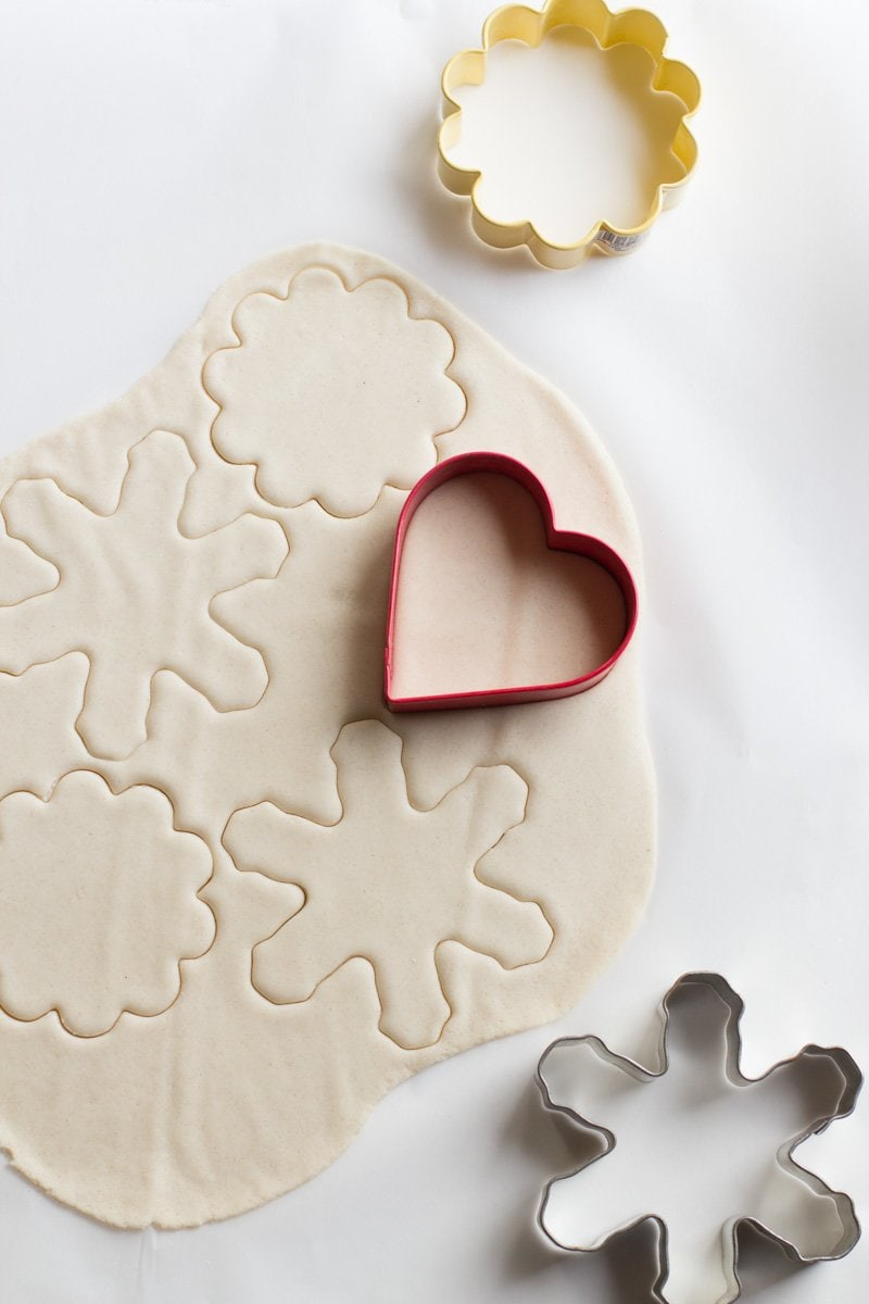 Cookie cutters are used to cut shapes for salt dough ornaments out of a piece of salt dough on a white background.