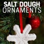 "A snowflake shaped salt dough ornament hangs from a red ribbon a Christmas tree. A text overlay reads ""How to Make Salt Dough Ornaments"""