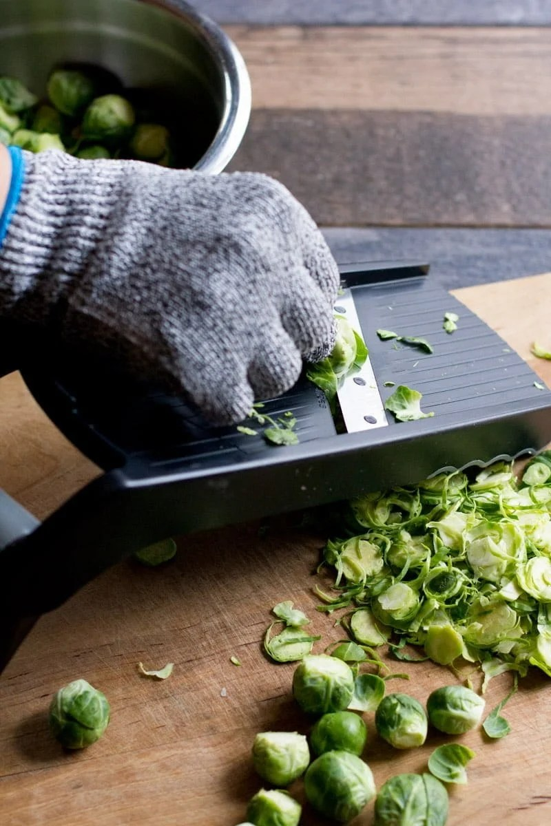 A gloved hand uses a mandoline to slice Brussels sprouts.