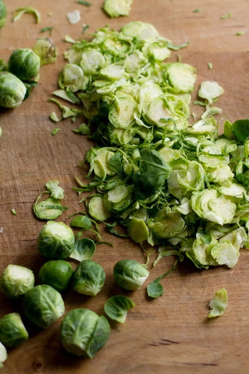 Brussels sprouts are piled on a wooden cutting board. Some of the sprouts are already shaved, and others are whole.