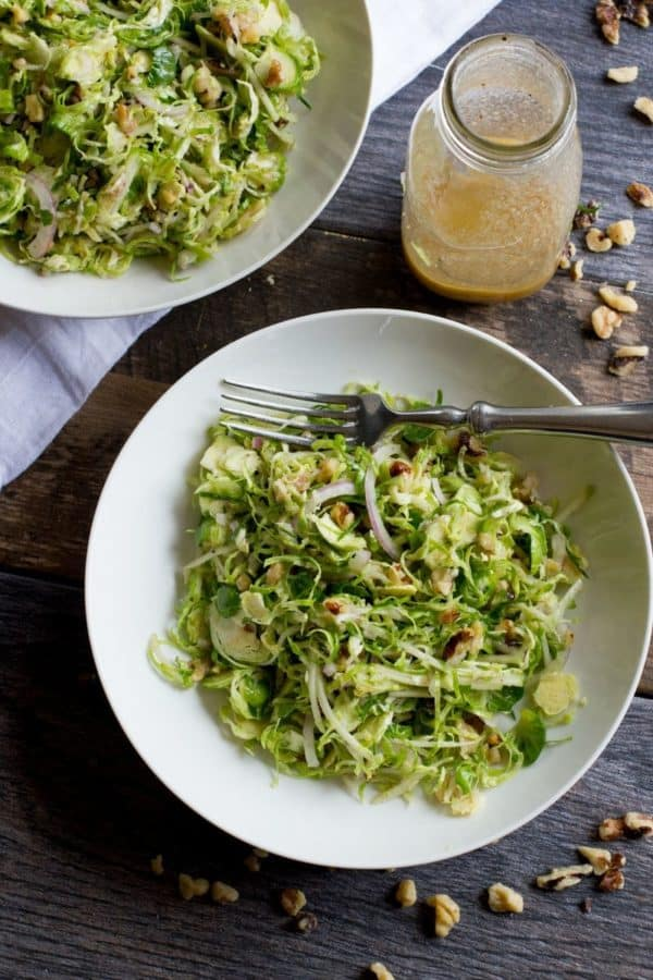 Shaved Brussels Sprout Salad with Apples and Walnuts in a white bowl with a fork.
