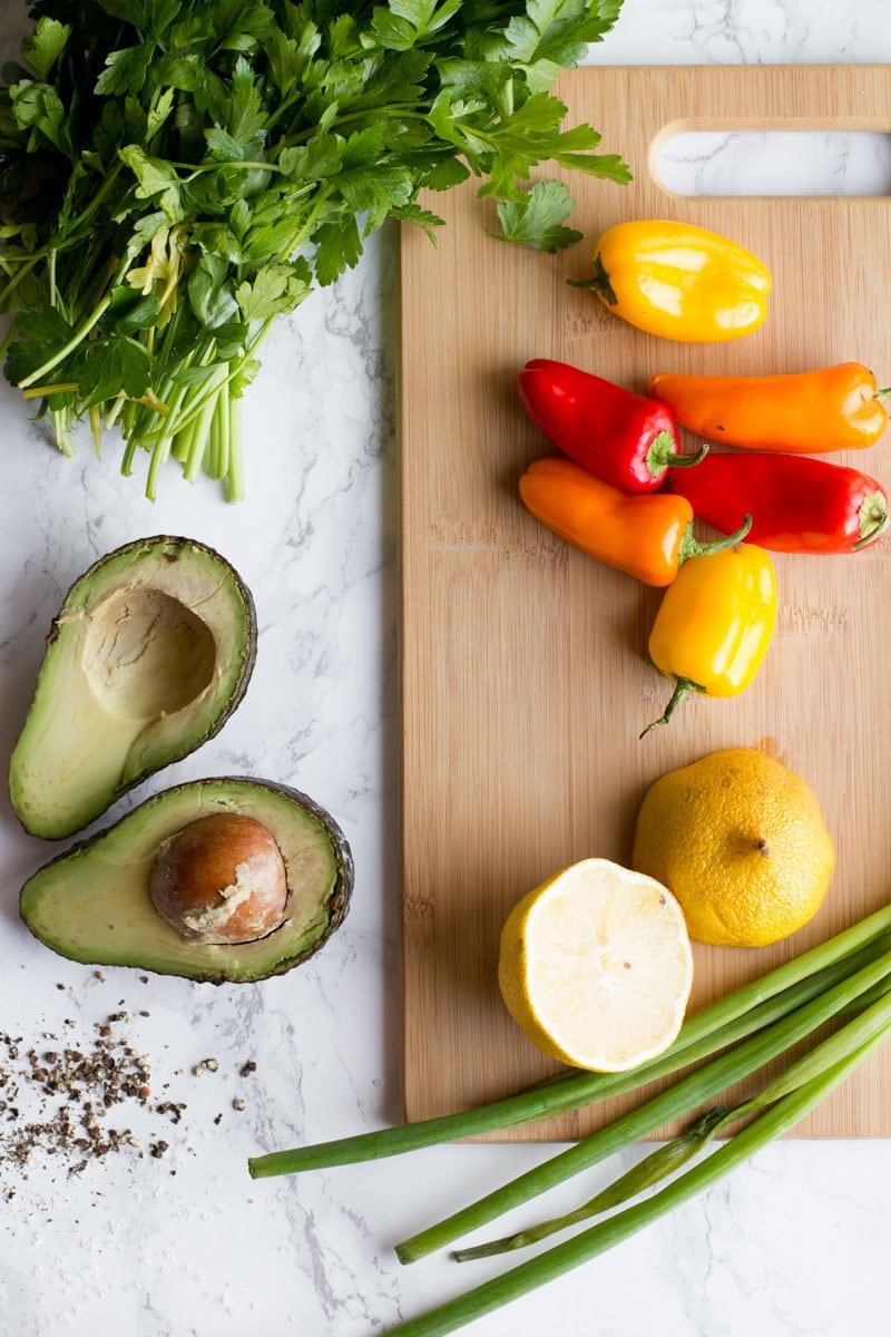 peppers, onion, lemon, cilantro and avocado sit on a wooden cutting board.