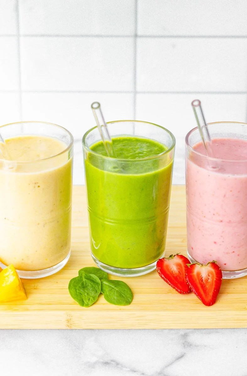 Three fruit smoothies are lined up in clear glasses with glass straws.