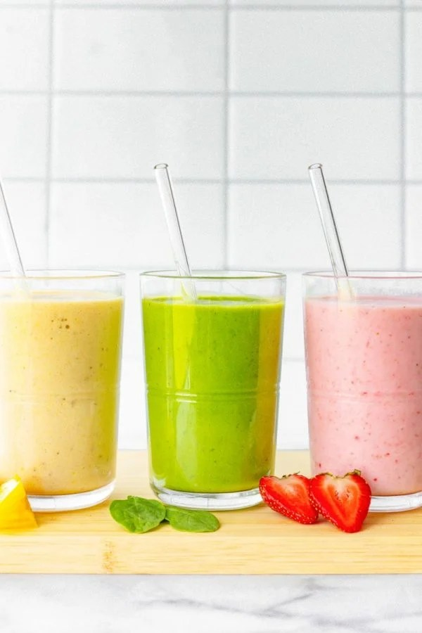 Three colorful fruit smoothies are lined up, each with a glass straw sticking out of it.
