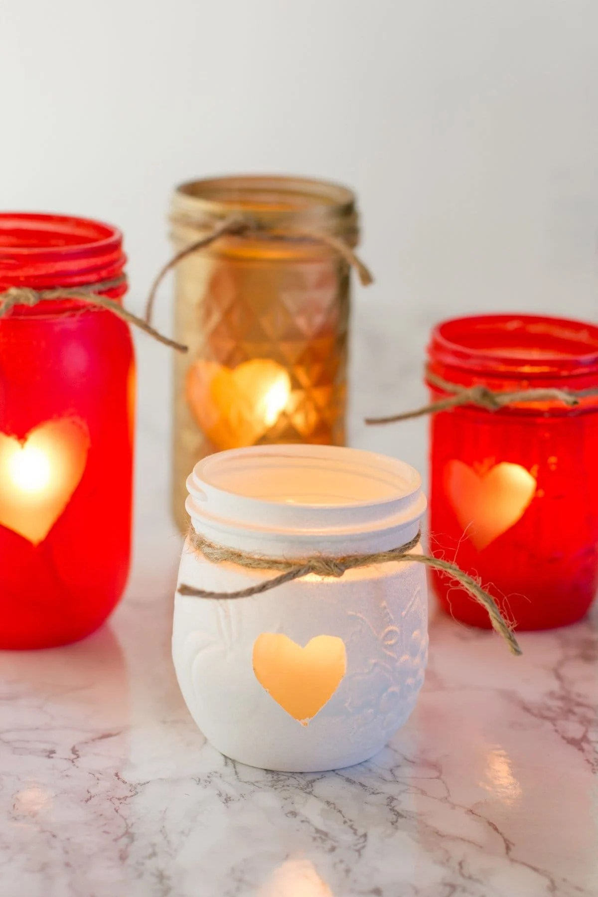 Cluster of Painted Mason Jar Votive Holders, each with a heart and a piece of twine. The jars are gold, red, and white.