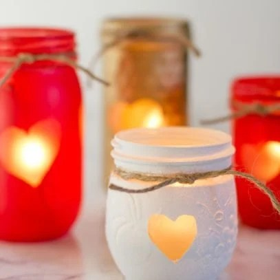 Four Painted Mason Jar Votive Holders painted for Valentine's Day, each with a piece of twine around the edge