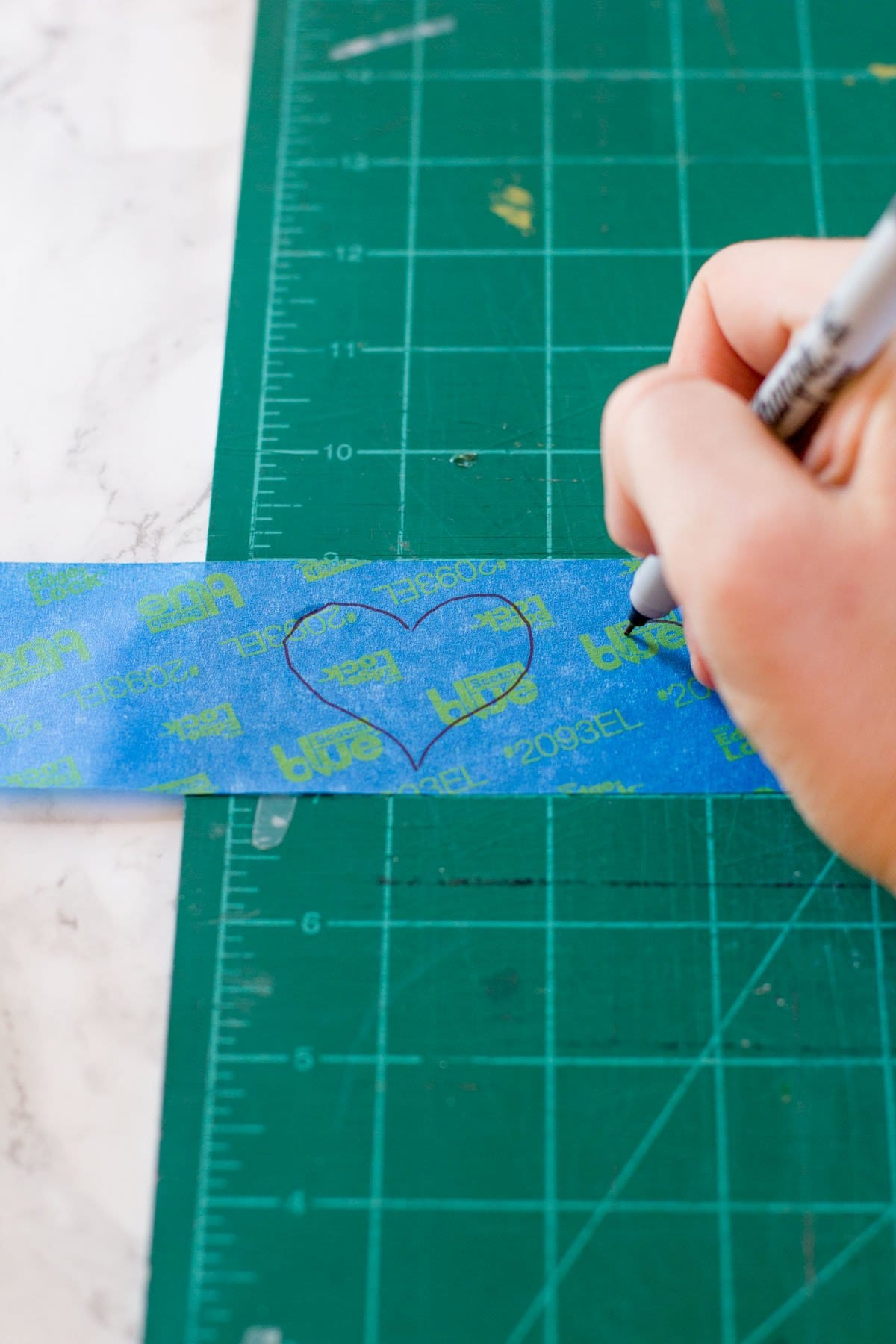 Hand using a Sharpie to draw hearts on a piece of painter's tape