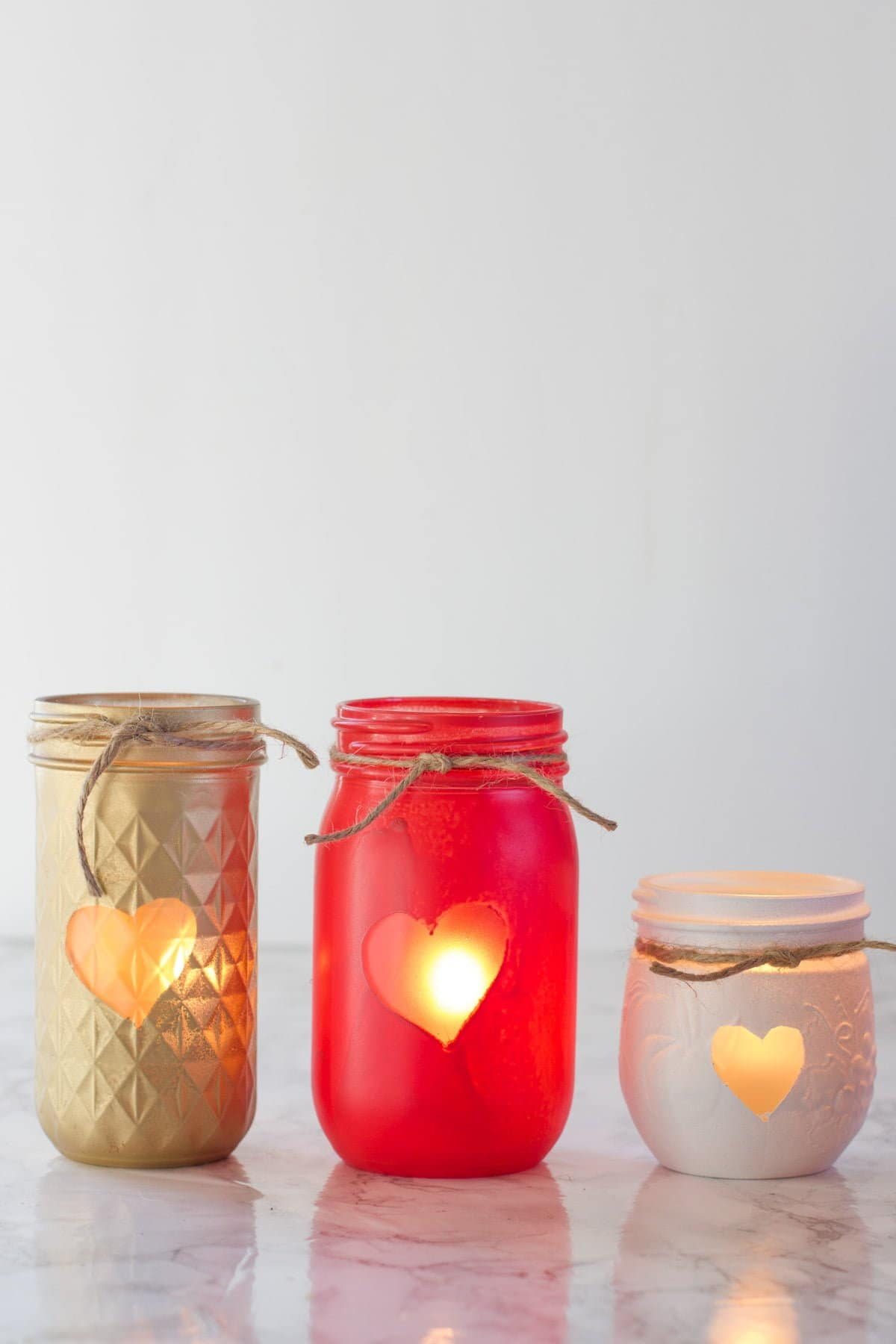 Three Painted Mason Jar Votive Holders, each with a heart and a piece of twine. The jars are gold, red, and white.