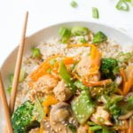 "Overhead shot of Healthy Chicken Stir Fry on top of brown rice in a white bowl with crossed chopsticks. A text overlay reads ""Healthy Chicken Stir Fry."""