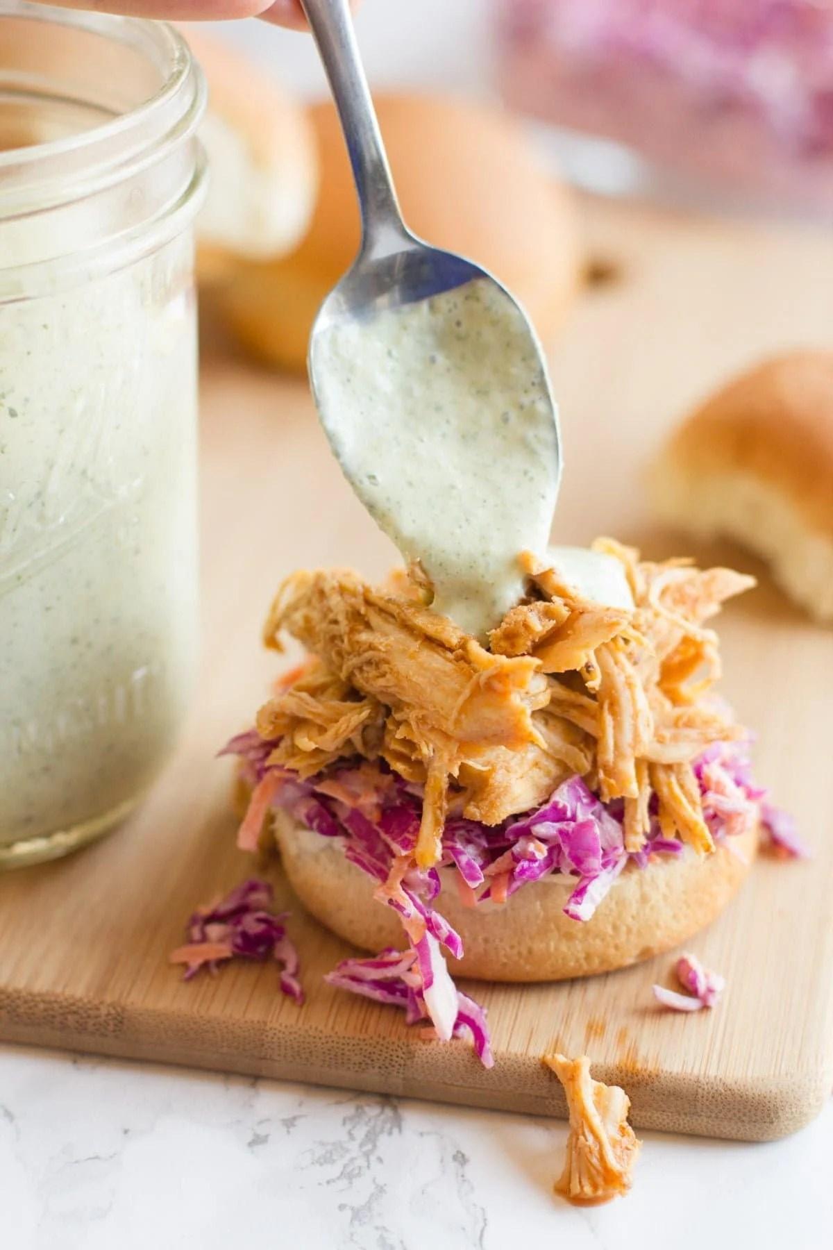 A spoon drizzles greek yogurt ranch sauce onto the top of a sriracha chicken slider.