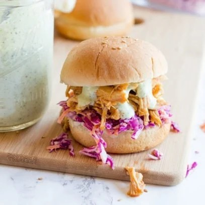 A slider topped with slaw, sriracha chicken, and ranch sauce sits atop a wooden cutting board on a marble counter.
