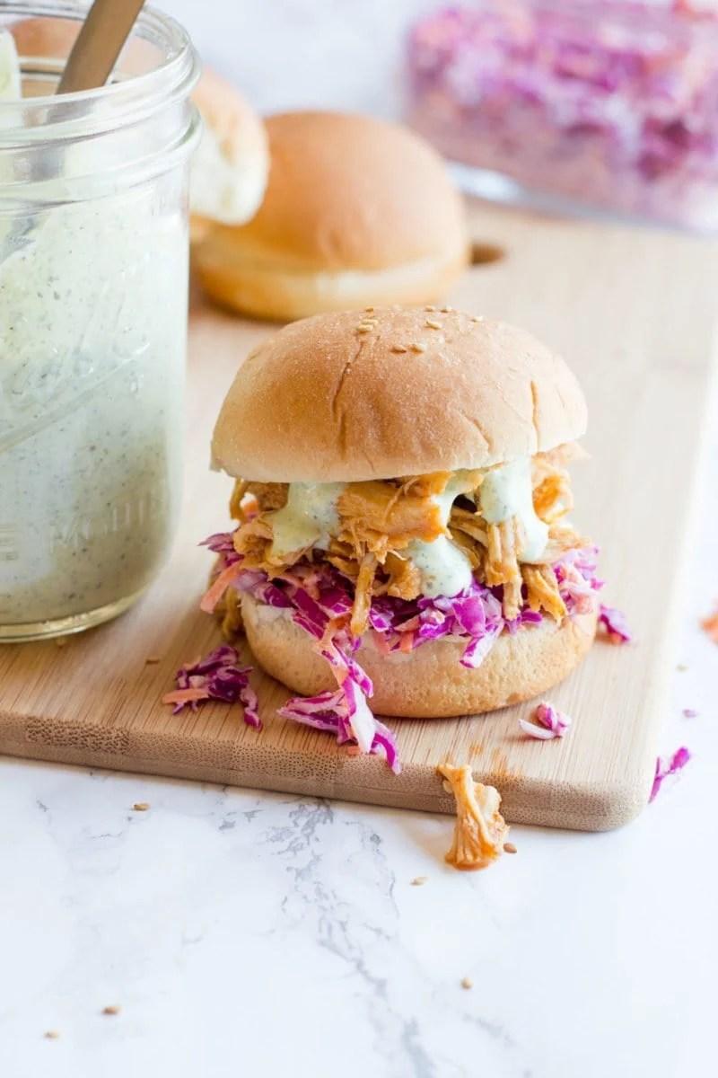 Slow Cooker Sriracha Chicken Sandwiches sit on a wooden cutting board near a mason jar of ranch sauce.