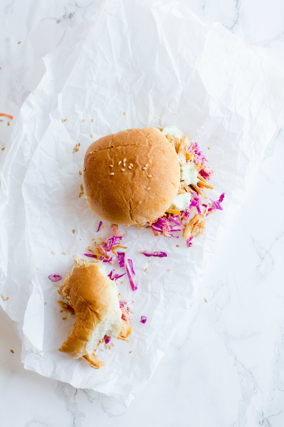 Overhead of two sliders on parchment paper, one of which is partially eaten.