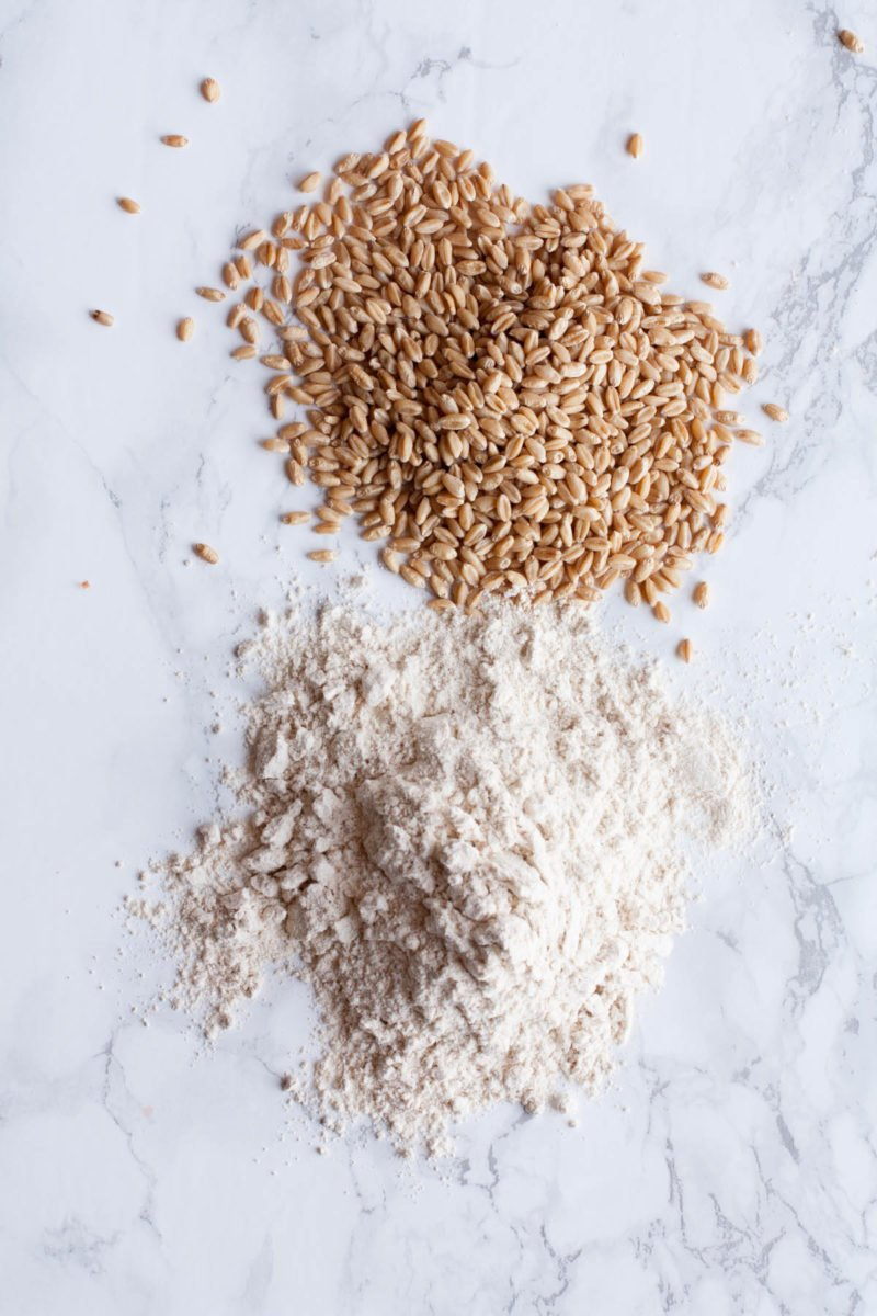 Wheat kernels and ground flour sit in two piles on a marble background.